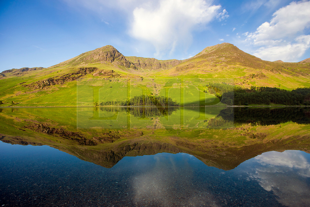 © Licensed to London News Pictures. 07/06/2018. Buttermere UK. Mountains around  Buttermere lake reflect into the still water this morning on a sunny day in Cumbria. Photo credit: Andrew McCaren/LNP