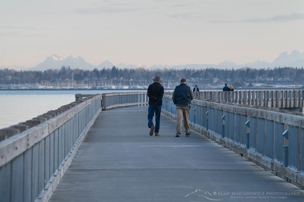 Two adult males walking on Boulevard Park Boardwalk, Taylor Dock on Bellingham Bay, Bellingham Washington