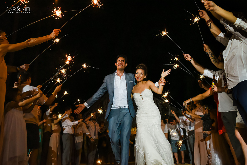 Stefanie & Jesse enjoying a spectacular moment during their walk under the sparklers at their reception in San Pancho, Nayarit. Photo by: Juan Carlos Calderón.