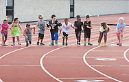 Middletown, New York - Children line up to start a race during the Twilight Track and Field Series run by the Middletown High School Varsity track program on July 22, 2014.