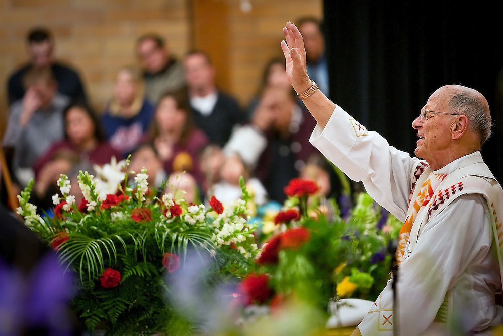 JEROME A. POLLOS/Press..Father Thomas Connelly says a prayer during the memorial service Thursday for Tim Wolfe.