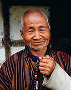 Monk with prayer beads, Shingkhey Village, Bhutan. From Peter Menzel's Material World Project.