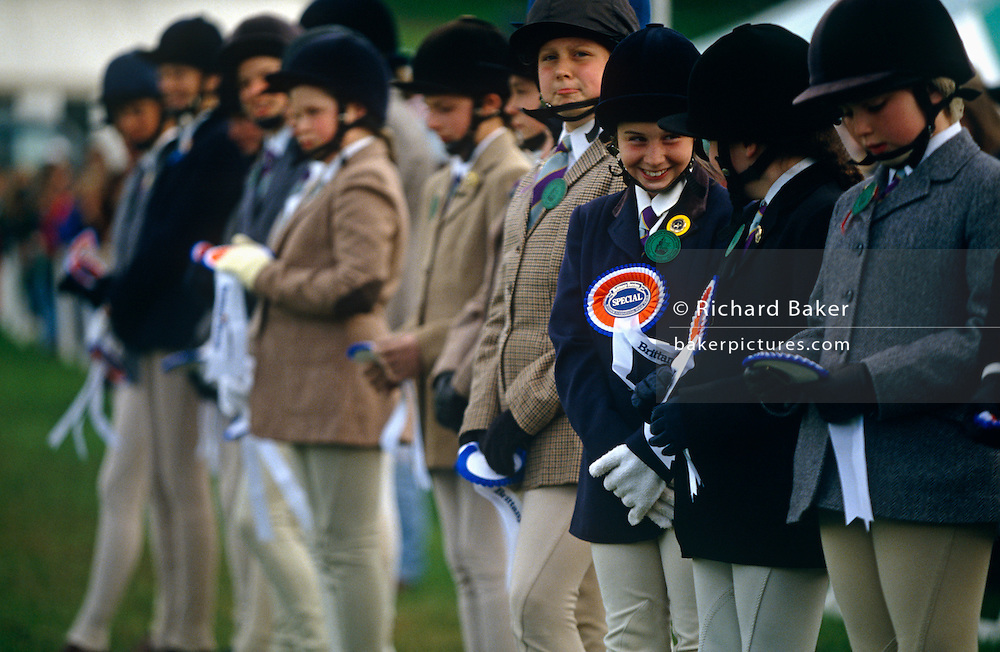"Winning and losing contestants line up to receive their prizes at a gymkhana in Cheltenham, Gloucestershire. The point of focus is a young cheeky-faced girl adorned with a winners' special rosette and she grins cheekily to her friend alongside. Far right another girl less satisfied inspects her own rosette. The word gymkhana is an Indian Raj term that referred to a place where sporting events took place to test the skill of the competitors. In the UK and east coast of the US, the term gymkhana now almost always refers to an equestrian event for riders on horses, often with the emphasis on children's participation (such as those organised here by the Pony Club). Gymkhana classes include timed speed events such as barrel racing, keyhole, keg race (also known as ""down and back""), flag race, and pole bending."