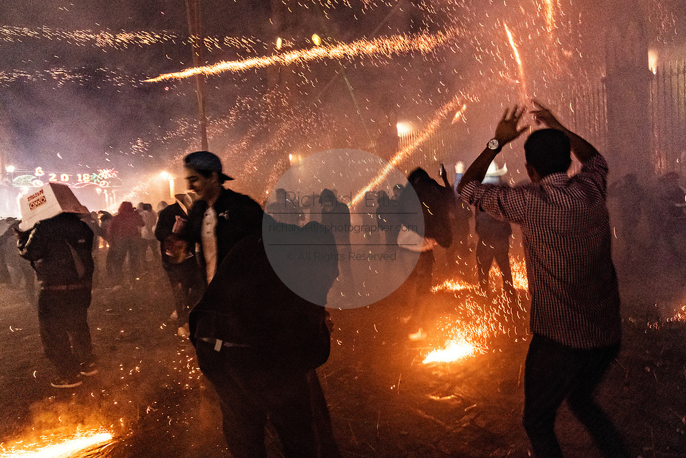 Mexicans run for cover as they are barraged by pyrotechnic sky rockets during the Alborada festival September 29, 2018 in San Miguel de Allende, Mexico. The unusual festival celebrates the cities patron saint with a two hour-long firework battle at 4am representing the struggle between Saint Michael and Lucifer.