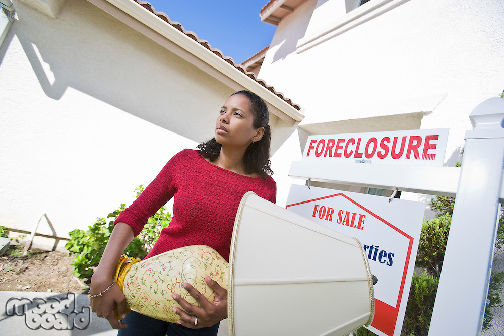 Sad mid adult woman moving out of house