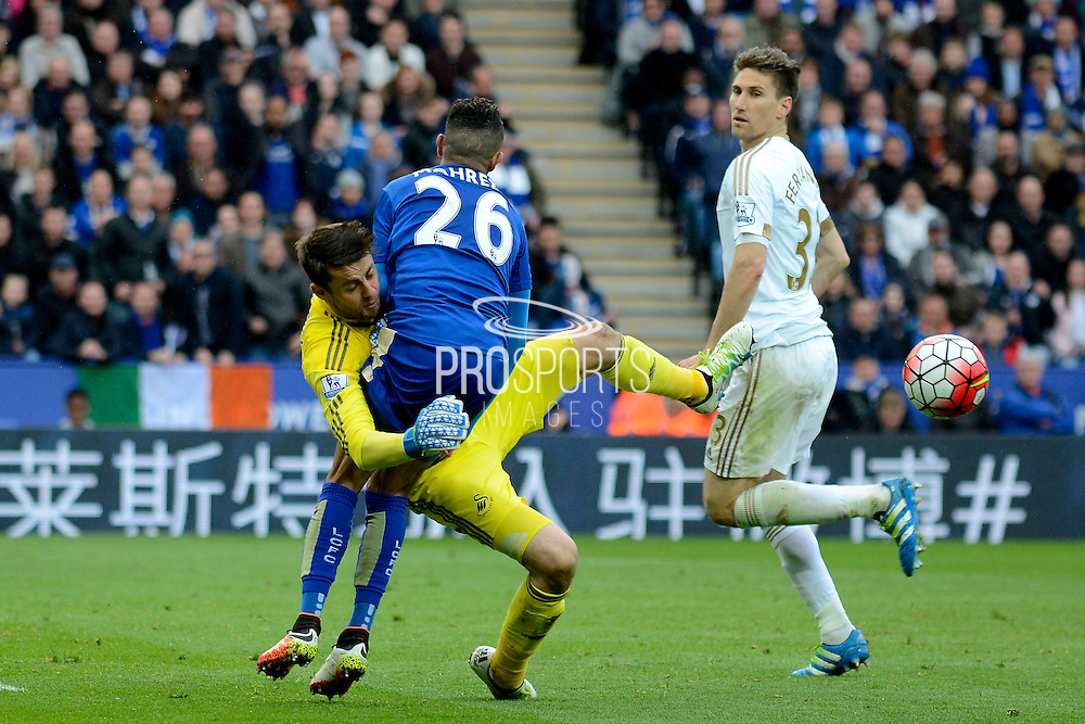 Swansea City goalkeeper Lukasz Fabianski clashes with Leicester City midfielder Riyad Mahrez during the Barclays Premier League match between Leicester City and Swansea City at the King Power Stadium, Leicester, England on 24 April 2016. Photo by Alan Franklin.