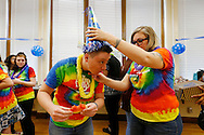 "Jack Schuler (left) ducks down as Stephanie Brennan, a family consumer sciences teacher, puts a party hat on Schuler's head Friday, May 20, 2016, during an ""It's a Boy"" party in his honor at Lincoln High School in Des Moines. Schuler started the school year as Elyse Schuler before coming out as transgender to his students and coworkers."
