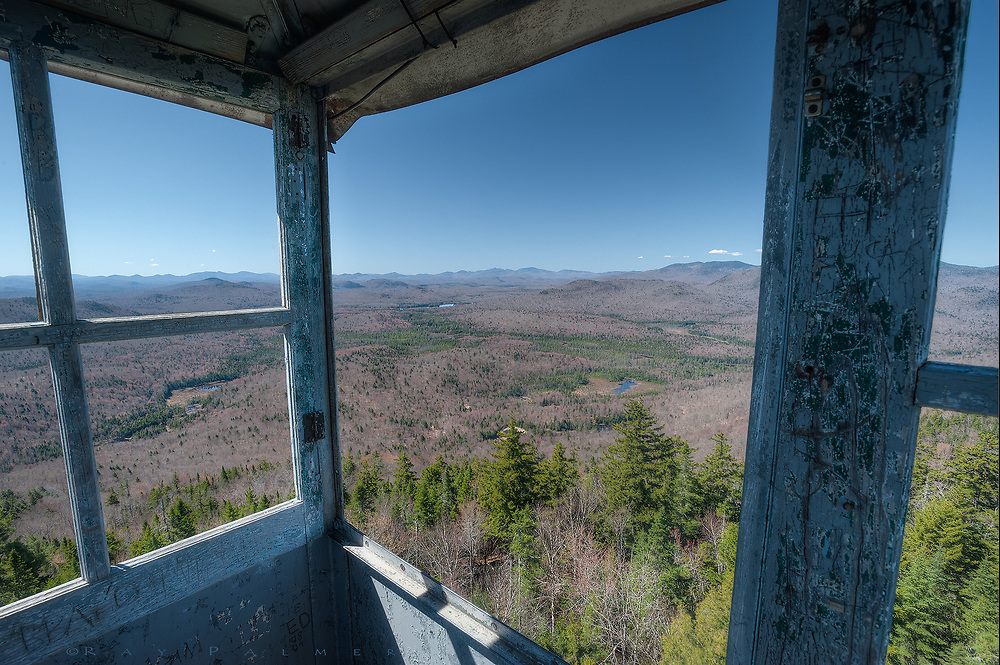 Goodnow Mountain, Adirondacks, NY<br /> While processing this, I was thinking about the irrational problem I always have going up one of these towers.  I&rsquo;ve often put myself at risk for shots, because I'm always looking for perspective.  I&rsquo;ve learned to overcome a fear of heights&hellip;but I still have trouble with certain situations.  Ladders, after a certain point, rope bridges, and fire towers among them.  I&rsquo;ve been up most, but my imagination wreaks havoc on me going up.  To the point that I often retreat down, talk some fortitude into my brain, and go back up.  It may be the open levels of weathered, wooden stairs&hellip;wondering if one will give way on my next step.  Or thinking about the bolts that hold the legs to bedrock; how taut the guy wires may be;  is it the handrail that&rsquo;s rattling unattached somewhere?  It's the exposure, or the perception of it, that unnerves me.  I don&rsquo;t feel the same vulnerability on cliff ledges, or canyon trails, or scaling a steep mountain trail.  Once I am through the hatch and into the cab it all disappears.  I take control of exposure, in a different sense.  For all my fear of climbing the last couple of levels, I am rewarded with the unveiling of compass points in very direction.  It is for me to reveal the scene before me, to capture the relation of shadow and light onto the medium of film or digital card.  I frame it as I want the story told.  On this day, before spring can dodge and burn the land in a sea of green, the bare forests and wetlands roll away from me to a horizon of peaks cloaked in distance.  With it&rsquo;s vast forests and meadowlands cut by rivers and sprinkled with wetlands, it is a complicated nakedness, a confession presented to me each time I see it, not unlike my own.
