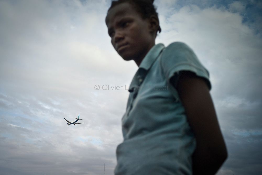 The number of cholera victims in Cité Soleil, a slum of Port-au-Prince, is increasing day by day exponentially, according to a doctor of Doctors Without Borders, essentially because of hygienic problems./// A woman stands close to the Cite Soleil's harbor in Port-au-Prince, while a plane flies over the Capital of Haiti.