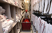 Equipment managers work in the Mal Moore Athletic Facility to get the University of Alabama football team ready for the trip to Baton Rouge to face LSU.  Student manager Thomas Hall pushes a cart of uniforms between shelving units that can be moved to save space in the equipment room.  Photo by Gary Cosby Jr.