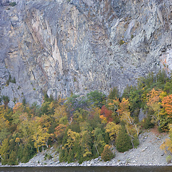 Fall foliage below the cliffs on Mount Kineo on Moosehead  Lake Maine USA