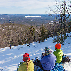 Three women take in the winter view from Hanson Top on Green Mountain in Effingham, New Hampshire.