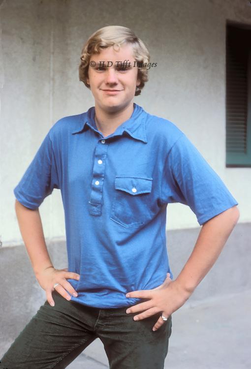 Wearing a blue shirt and a slightly arrogant half smile, three quarter length shot, hands on hips.
