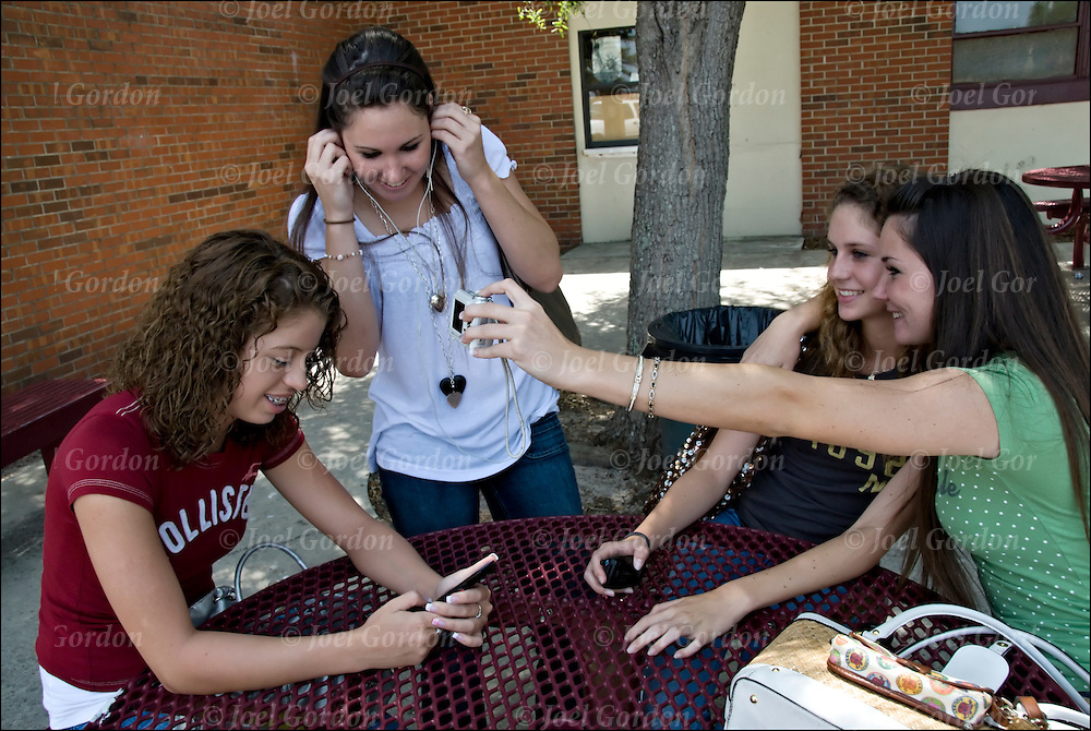 A group of female students sitting outdoors on table during lunch period hanging out, talking, texting and taking photo of each other at at the Crescent City Jr. and Sr. High School in Florida