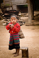 Laos, nearby Luang Nam Tha. Little Khamu girl with a bag on her head.