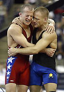Brandon Paulson (red) laments losing the Greco Roman 55 kg class to Dennis Hall (blue) at the 2004 U.S. Olympic Wrestling Trials.  Hall defeated Paulson in three matches.  The third lasted 16 minutes and 54 seconds.
