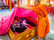 "29 MARCH 2017 - BANG KRUAI, NONTHABURI, THAILAND: A Buddhist monk pulls a pink sheet over a family in a coffin, symbolizing their death during a ""Resurrection Ceremony"" at Wat Ta Kien (also spelled Wat Tahkian), a Buddhist temple in the suburbs of Bangkok. People go to the temple to participate in a ""Resurrection Ceremony."" Groups of people meet and pray with the temple's Buddhist monks. Then they lie in coffins, the monks pull a pink sheet over them, symbolizing their ritualistic death. The sheet is then pulled back, and people sit up in the coffin, symbolizing their ritualist rebirth. The ceremony is supposed to expunge bad karma and bad luck from a person's life and also get people used to the idea of the inevitability of death. Most times, one person lays in one coffin, but there is family sized coffin that can accommodate up to six people. The temple has been doing the resurrection ceremonies for about nine years.          PHOTO BY JACK KURTZ"