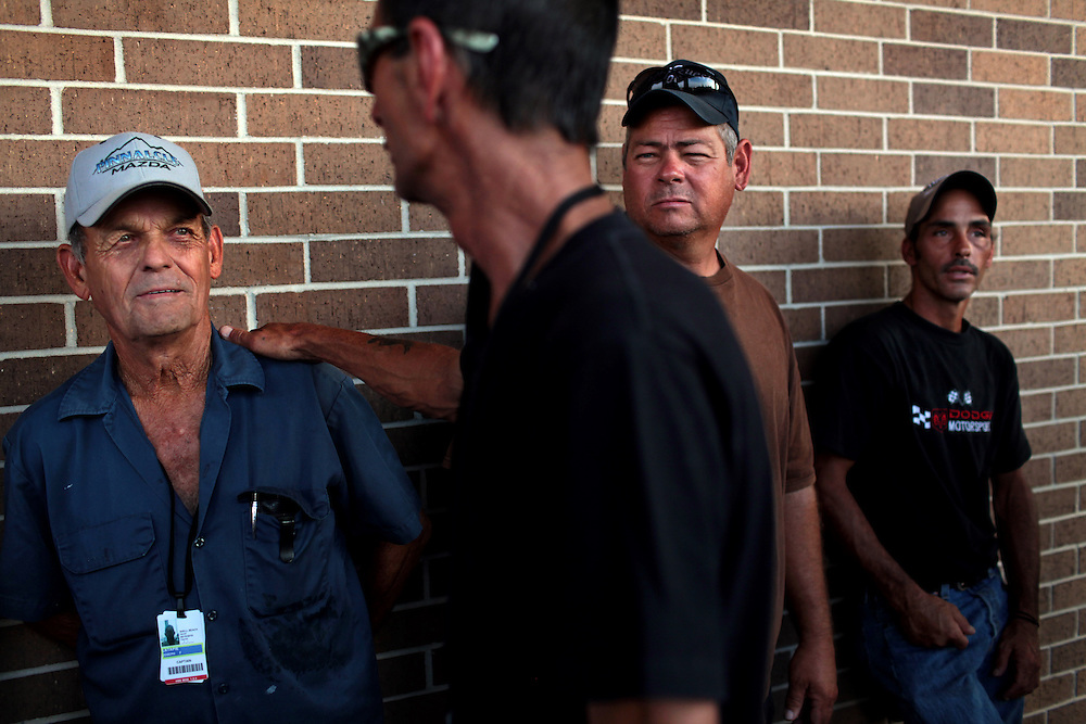 Commercial shrimp boat captain Joseph Latapie, 72, left, with his son Travis Latapie, right, talks with Richard Oracoy, foreground, while Manvel Meyer, far right, waits in line for their checks from BP before the Public Meeting at the Frederick J. Sigur Civic Center Ballroom in Chalmette, Louisiana on May 24th, 2010. Over 500 fishermen and their families waited in line for over five hours in sweltering heat for their checks from BP.