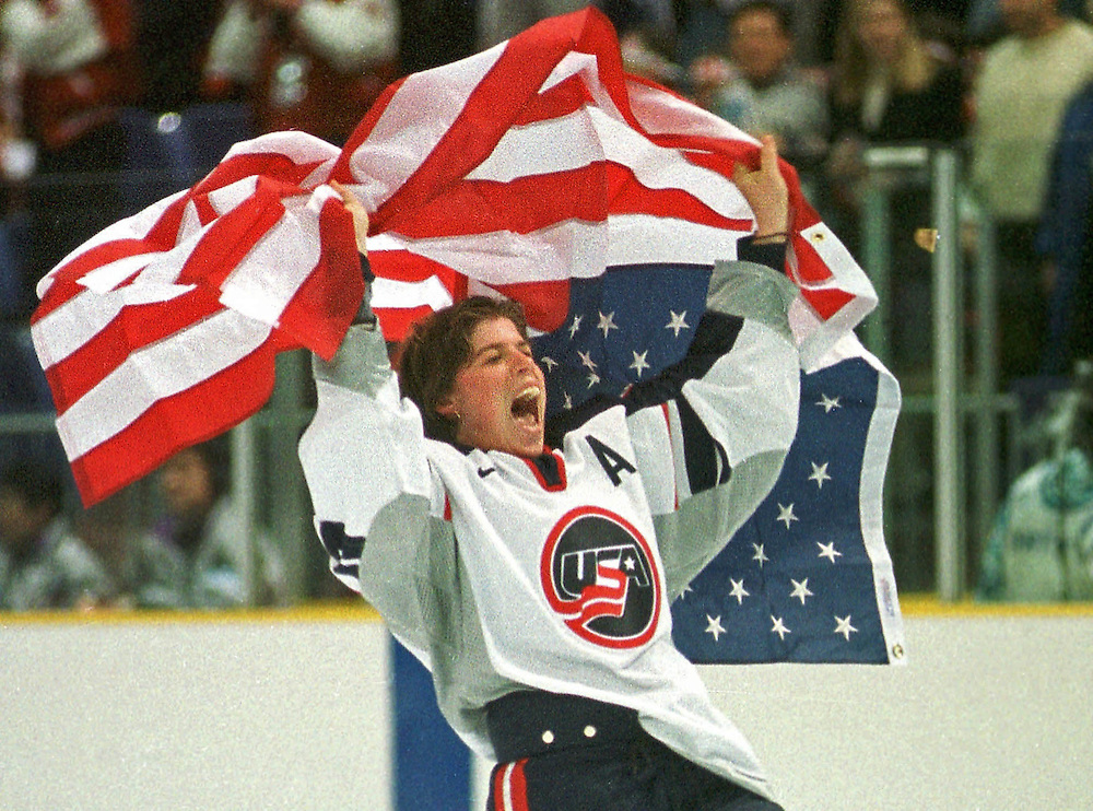 Karyn Bye holds up a US flag after her team won the gold medal in the 1998 Nagano Olympic Winter Games.  Photo by August Miller