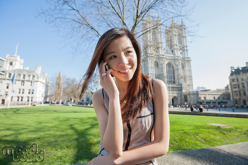 Happy woman using cell phone against Westminster Abbey in London; England; UK