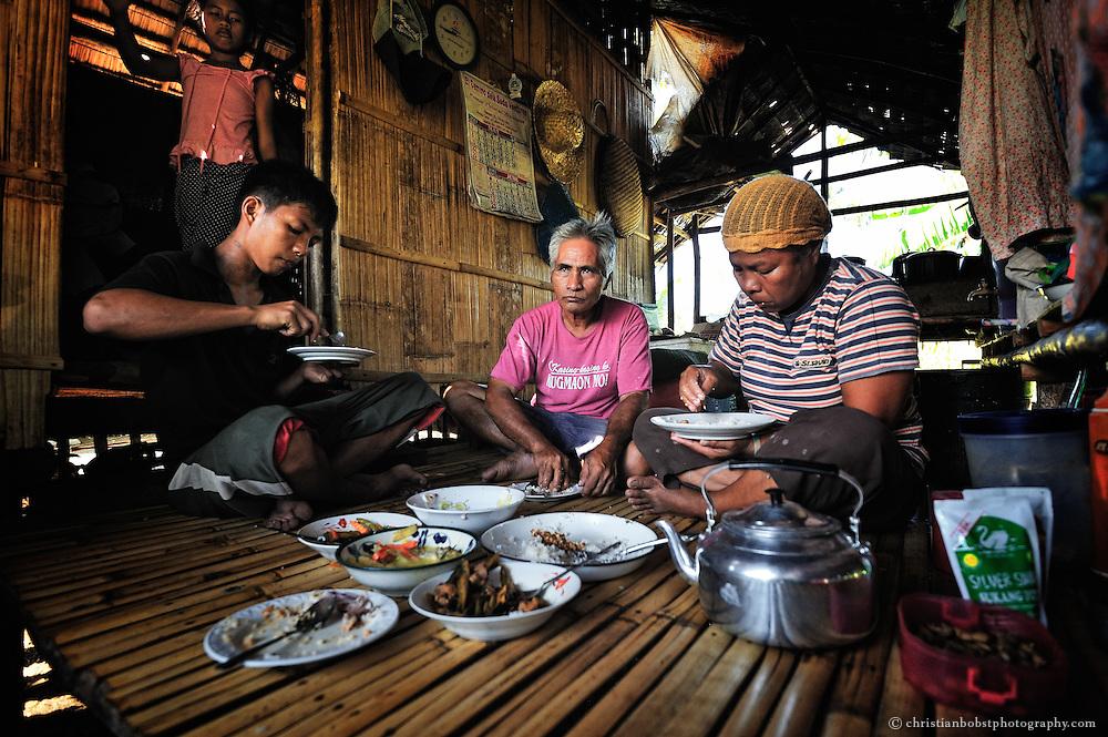 Alma, ihr Mann Carlito und Sohn Nhorjaed  beim gemeinsamen Mittagessen. Die Zutaten für das Essen stammen grösstenteils vom eigenen Boden. Vom Geld, welches sie mit dem Verkauf der Cpra verdienen, können sie die nötigen Dinge des Alltags wie zB. Kleider, Schuhe sowie Schulmaterial bezahlen.