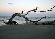 Red head woman walking Driftwood Beach at sunset