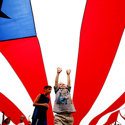 Kyle Green | The Roanoke Times<br /> April 15, 2006 Four year old, Strider Mitchell (middle, arms raised), from Blueridge, runs underneath a giant flag unfurled during the &quot;Rally Round the Flag&quot; ceremony at the The 8th Annual Blue Ridge Kite Festival held at Green Hill Park in Salem, Virginia on Saturday afternoon.