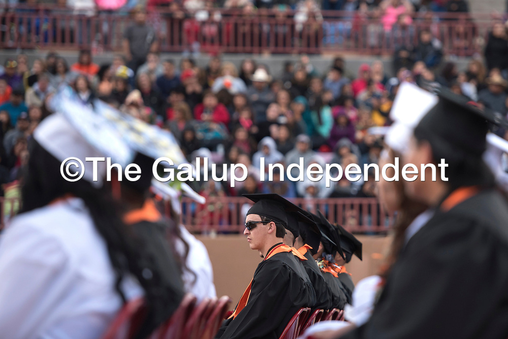051515      Cayla Nimmo<br /> <br /> Joshua Tyler Randolph listens to the valedictorian speeches during the Gallup High School Graduation in Red Rock Arena Friday.