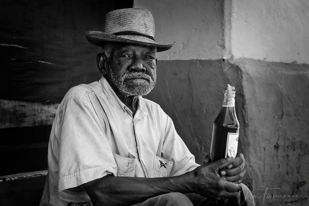 An old man enjoying a bottle of rum in the streets of Trinidad.