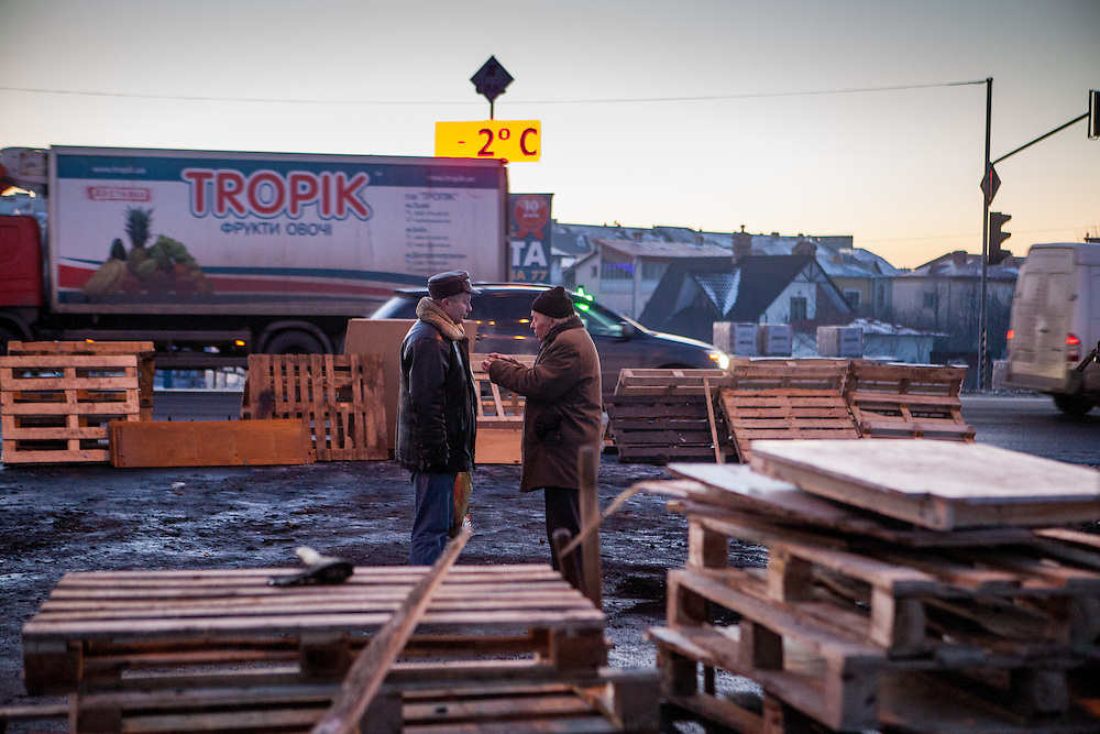 "Two passersby are discussing at the barrikades blockading a building supplies store named ""Epicenter"" in the city of Lviv, Ukraine."