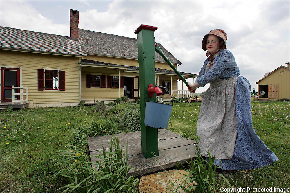 "mothers - des moines, may 8 -- In 1875 mothers didn't have the luxury of taking Sundays off - even on Mother's Day.  Lisa Elm, who works at Living History Farms and greets visitors at the Tangen Family Home, pumps drinking water Sunday.  ""This type of family would have typically had six children,"" said Elm.  Given that fact, it's not surprising that even Mother's Day couldn't have been a rest day.  photo by david peterson  miDes Moines, Ia."