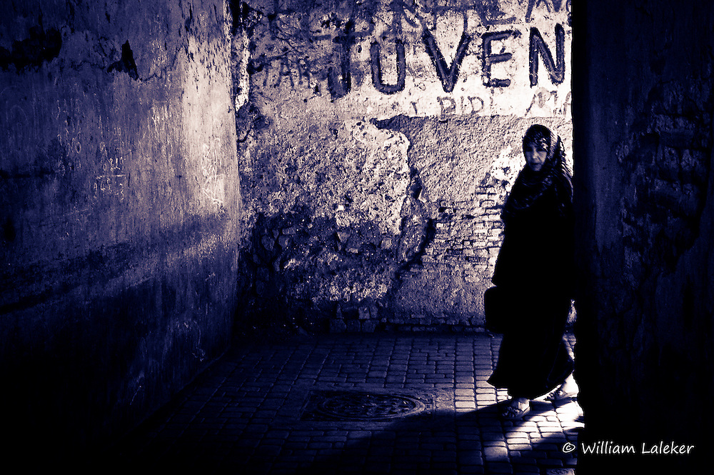 Women enter dark tunnel in the old city section of Marrakesh.