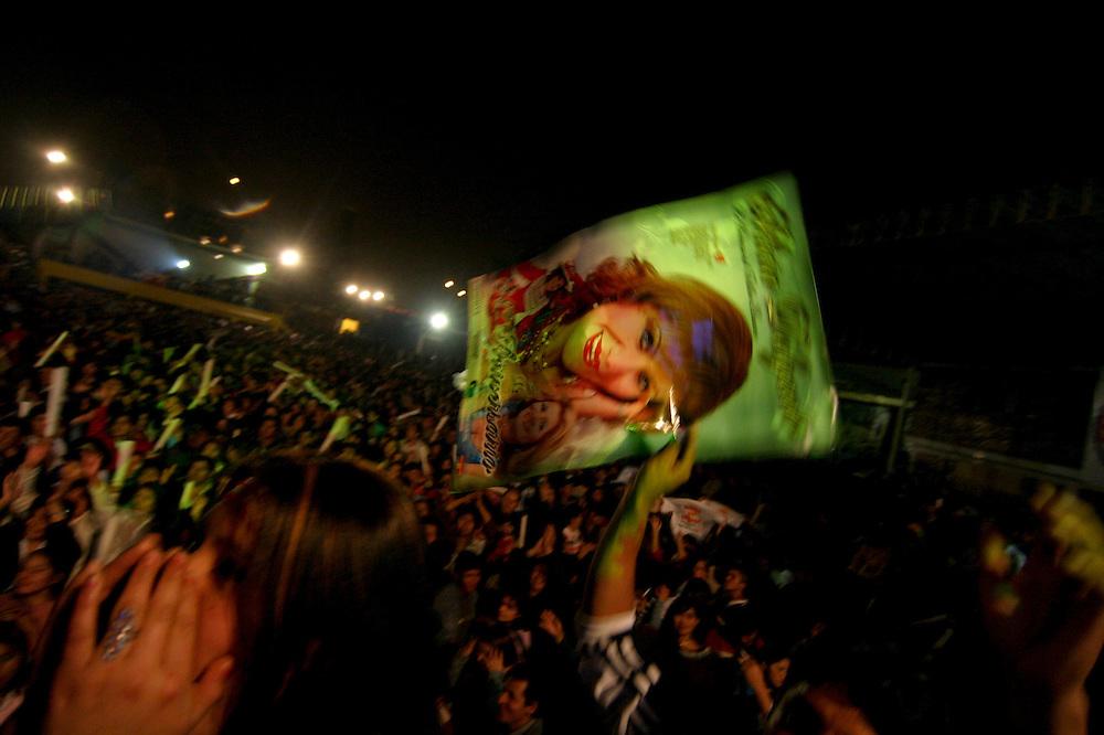 Asistentes al concierto bailan con el afiche de una cantante de huayno.