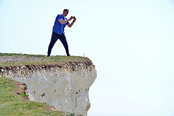 © Licensed to London News Pictures. 22/04/2019. Birling Gap, UK.  Reckless members of the public risk their lives on the edge of the crumbling chalk cliffs of the Seven Sisters near Eastbourne, UK. The iconic sheer white cliffs are up to 400 feet high and have had recent record cliff falls due to erosion, but many people, some even holding children, cannot resist the temptation to peer over the edge to get photos. Some people are even seen jumping in the air just feet from the edge.  Photo credit: Peter Cripps/LNP