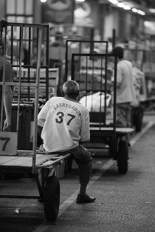A trolley carrying man takes a break at Rio's CADEG Market.