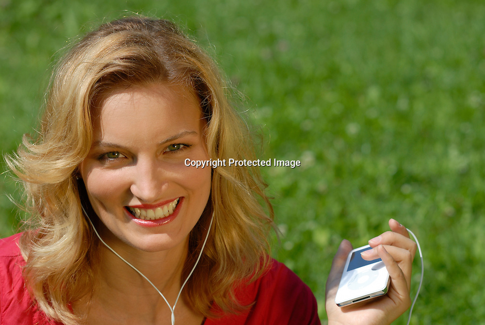 A beatiful blonde woman relaxing with an ipod mp3 player on her hand, listening to music