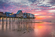 A pink and purple sunrise erupts behind the Pier at Old Orchard Beach, one of Maine's most recognizable landmarks.