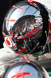 epa02120699 The grandstand and British Formula One driver Jenson Button of McLaren Mercedes' car is reflected in the helmet of a team member during the qualifying session at the Shanghai International circuit in Shanghai, China, 17 April 2010. The 2010 Chinese Formula One Grand Prix will take place on 18 April 2010.  EPA/HOW HWEE YOUNG