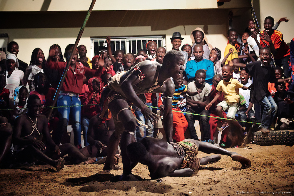 The spectators  go wild as a young wrestler defeats his opponent in a nightly competition on April 8, 2015 in the Ngor district in Dakar, Even small children attend the fights that often kick off until after midnight.