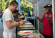 Brandon Peace of Rochester, right, serves Paul Stack of Rochester, a member of the Rochester AmeriCorps at Frontier Field in Rochester on Friday, July 31, 2015. Students from School #17 ate dinner at the stadium, and then camped on the field Friday night.