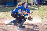 Middletown, New York - The Middletown catcher reaches for the ball as a Washingtonville player slides into home plate during a varsity girls' softball game on April 9, 2014.