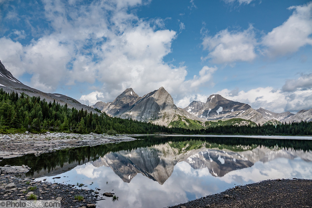 Lawson Lake reflects the limestone fangs of Mounts Maude, French (3244 m), and Jellico. Day hike from Forks Campground to North Kananaskis Pass (13 miles round trip/2700 ft) in Peter Lougheed Provincial Park, Kananaskis Country, Alberta, Canada.