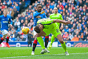 Darren McGregor (#24) of Hibernian FC heads the ball clear ahead of Jermain Defoe (#9) of Rangers FC during the Ladbrokes Scottish Premiership match between Rangers FC and Hibernian FC at Ibrox, Glasgow, Scotland on 5 May 2019.