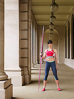 Female athlete holding javelin standing in portico portrait
