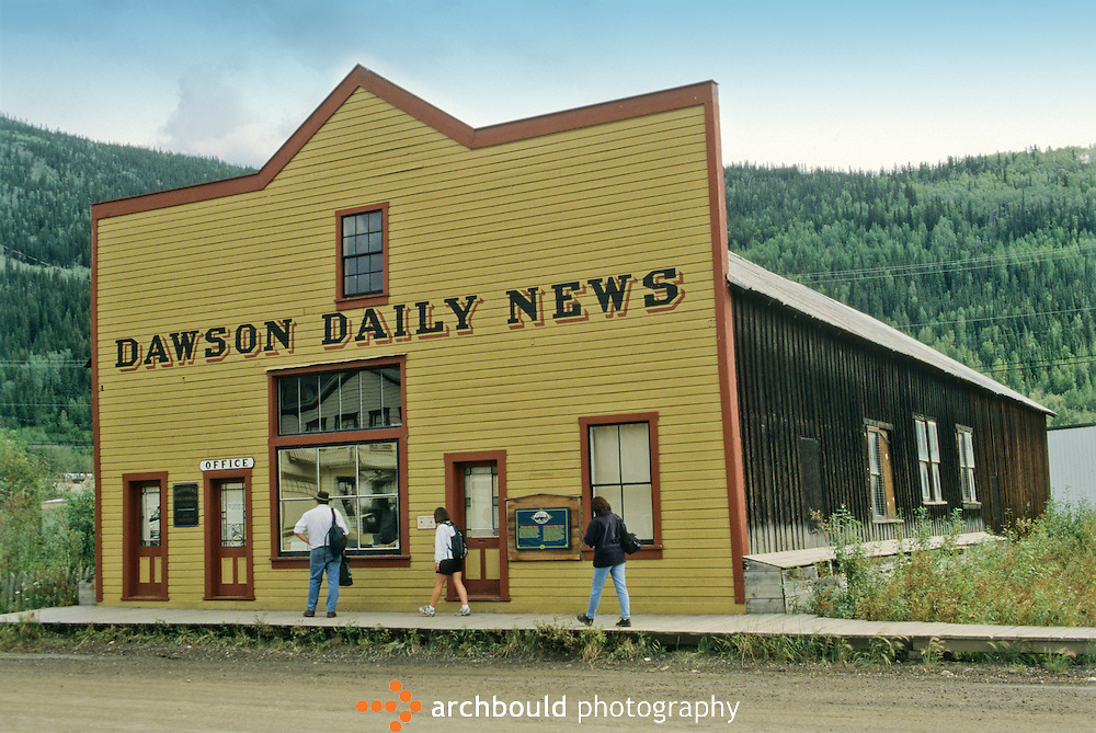 People walk in front of the Dawson Daily News, in Dawson City, Yukon