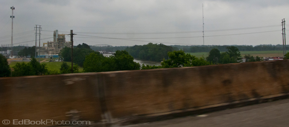 Bayou Teche and an industrial site viewed from US 90 Louisiana with the view partially obstructed by a highway barrier. panorama