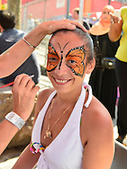 Brooklyn, New York, USA. 10th August 2013. This smiling young woman is having a  beautiful orange butterfly painted on her face by volunteer artist Laura Yorburg, during the 3rd Annual Coney Island History Day celebration.