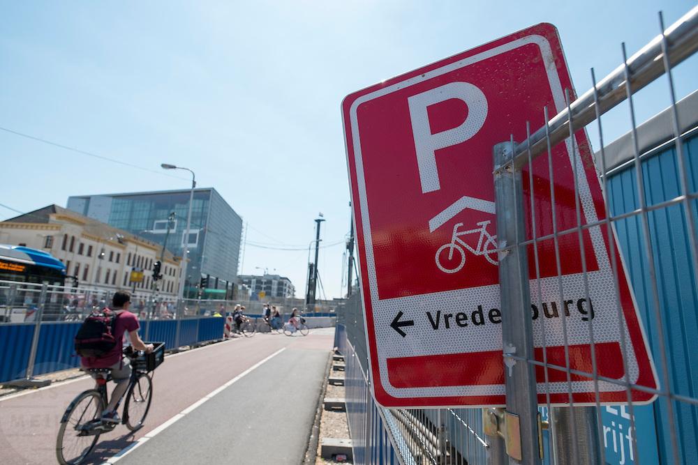 Bij het Smakkelaarsveld in Utrecht is het verkeersbord dat aangeeft waar de overdekte fietsenstalling staat weggestopt tussen de hekken van de bouwplaats.<br /> <br /> Near the Smakkelaarsveld in Utrecht the sign that indicates where you can park the bike tucked between the fences of a construction site.