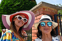 © Licensed to London News Pictures. 06/07/2018. LONDON, UK. Women buy sunhats from a vendor en route to the Wimbledon Tennis Championships from the nearest tube station, Southfields.  Temperatures forecast to approach 30C mean that the majority have taken precautions to protect themselves from the sun by wearing sunglasses and sunhats.  Photo credit: Stephen Chung/LNP