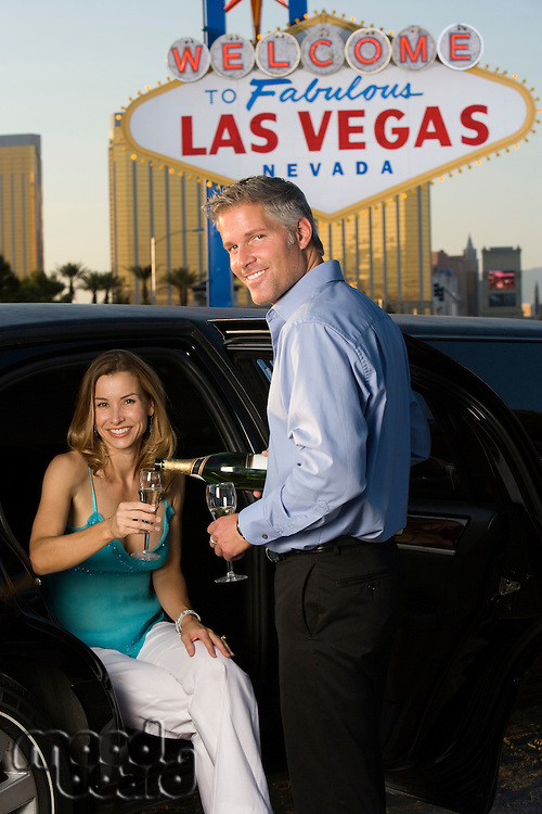 Mid-adult couple sitting in limousine and drinking champagne in front of Welcome to Las Vegas sign